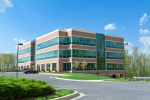 New office building in suburban Maryland, United States.  Parking lot in front of the building with several cars.